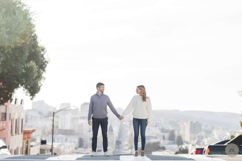 couple in pacific heights on engagement shoot with san francisco skyline in background