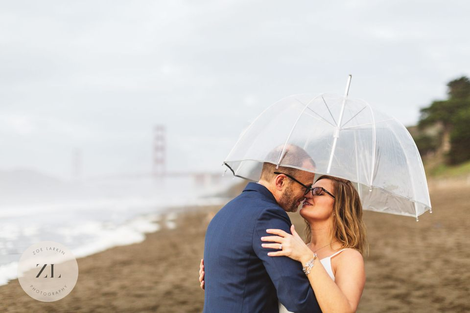 Wedding photos on Baker Beach, San Francisco with golden gate bridge obscured by fog