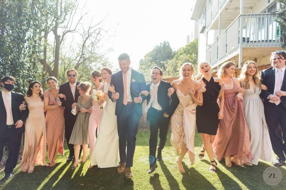 wedding party laughing and walking towards camera arm-in-arm at san francisco backyard wedding
