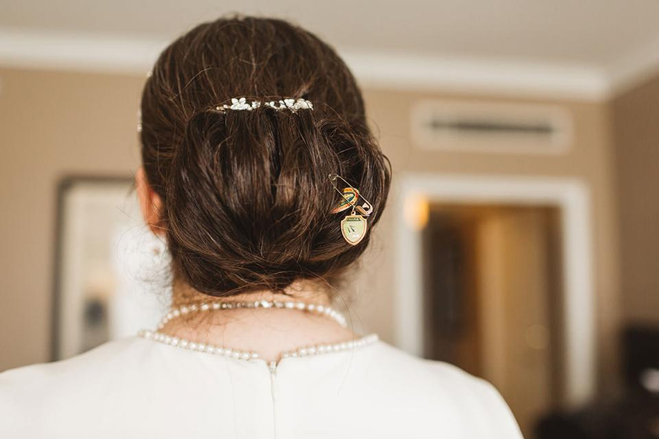 In the flurry of the big day, little details that you may want photographed can be easily overlooked unless you inform your photographer in advance so they can have a plan nailed down - image showing bride's military hair brooch
