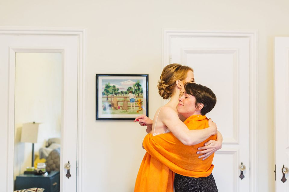 close friend hugging bride while getting ready on wedding day