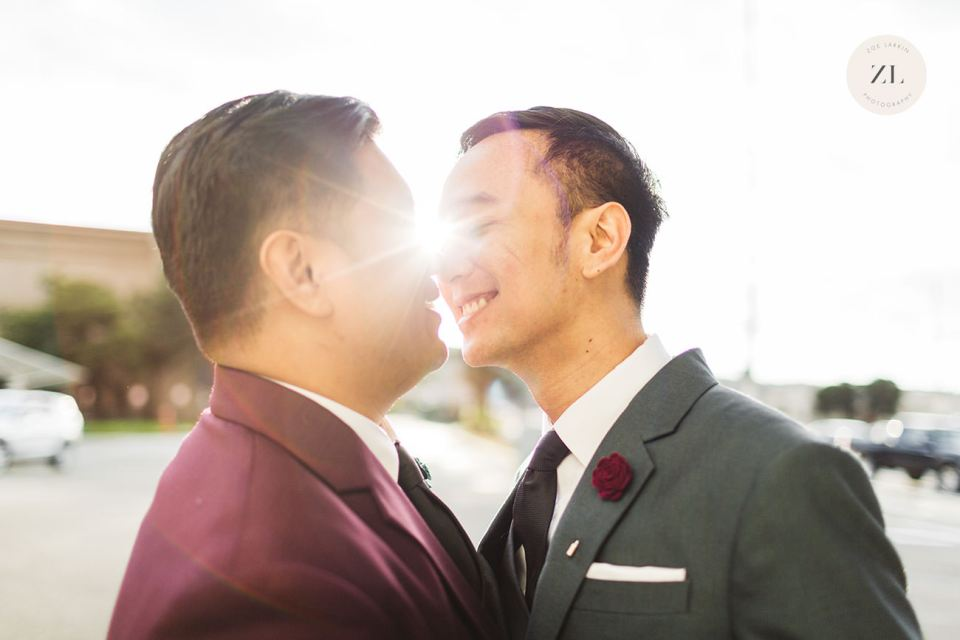 LGBTQ+ couple kissing on their relaxed and intimate wedding day with the sun flare behind them