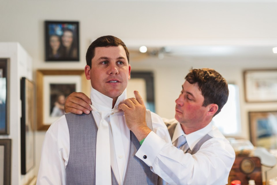 groom getting ready with help from groomsman