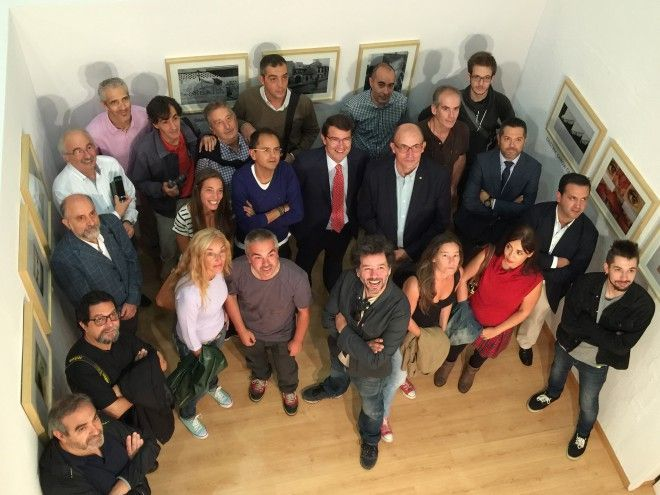 Los fotógrafos posan junto al alcalde y el presidente del Rotary Club en el acto de inauguración de la exposición.