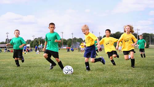 Niños jugando al futbol con su equipo