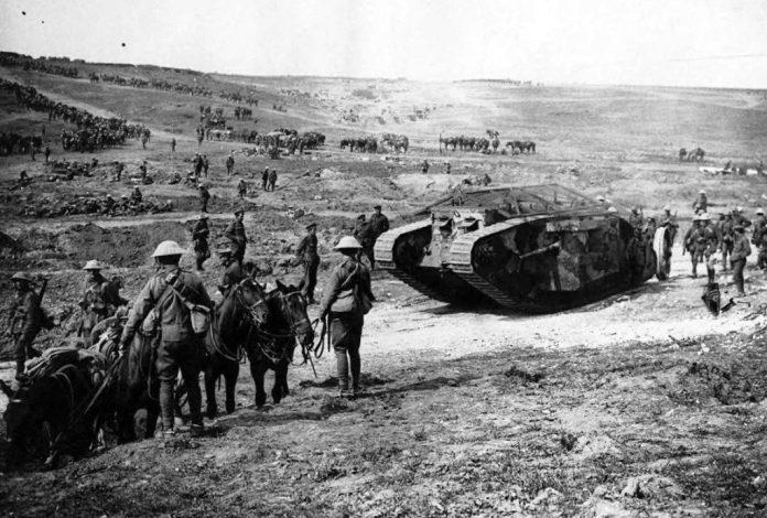Un tanque británico Mark V junto a soldados, caballos y mulas. El blindado ha sido debidamente pintado con un llamativo esquema de camuflaje. Imagen: National Library of Scotland.