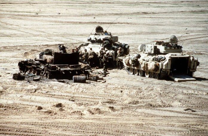Luego de la batalla, personal del US Army se agrupa junto a sus Bradley en torno a los restos calcinados de un tanque T-72. El M-2/M-3 Bradley demostraría durante la operación Desert Storm ser un excepcional VCI. Imagen: SSgt. Dean Wagner.
