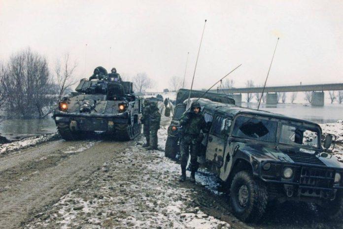 Soldados junto a sus HMMWVs observan el avance de una columna de Bradleys através del puente tendido sobre el río Sava, en el inicio de la operación Joint Endeavor. Imagen: Ward.