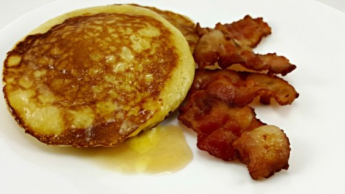 two pancakes with syrup and bacon