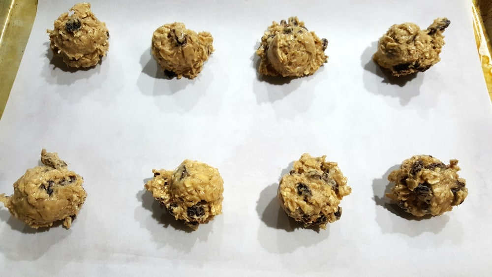 Soft Batch Oatmeal Raisin Cookies Recipe - cookie dough balls placed on a baking sheet