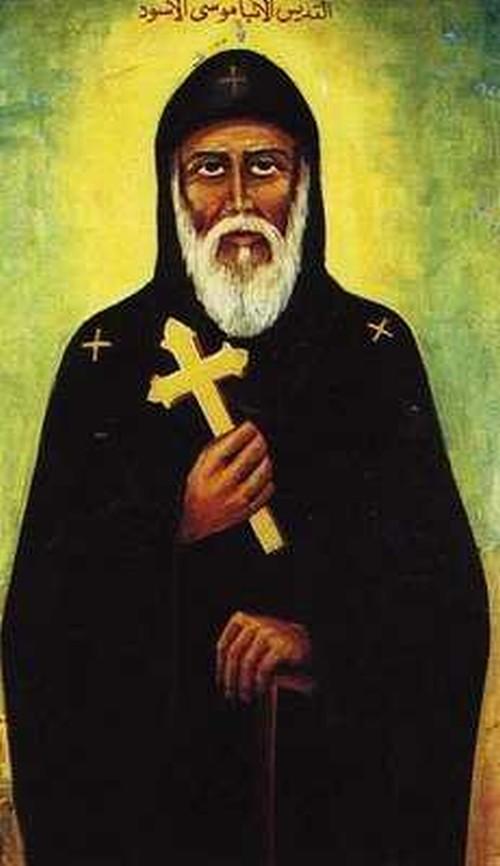 San Moisés el Negro mirando al frente sosteniendo una cruz y tiene un habito con capaucha