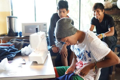 Joel sews a shirt seam while the boys watch.
