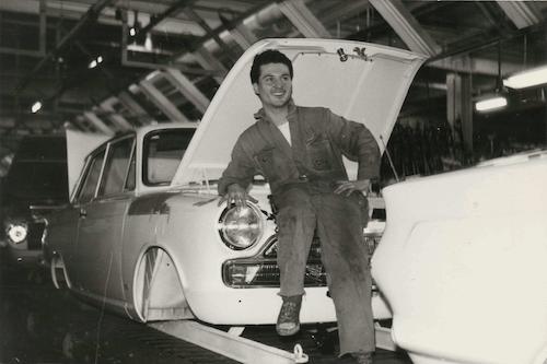 Antonio Valverde delante de un coche en la cinta de montaje en la fábrica Ford en Amsterdam (1963)