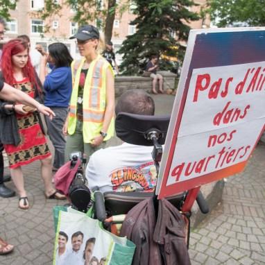 Manifestation contre AirBnB. Un homme en fauteuil roulant électrique porte une pancarte.