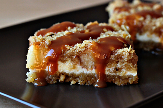 Caramel apple cheesecake cookie bars recipe with step by step pictures. Caramel apple cheesecake cookie bar on a brown plate.