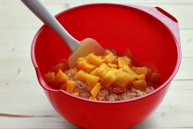 folding diced peaches in the muffin batter in a red whisking bowl