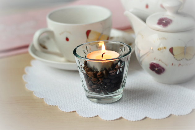 candle in glass with coffee beans