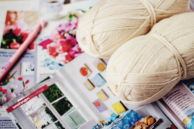 white yarn, crochet hook and colorful living magazines