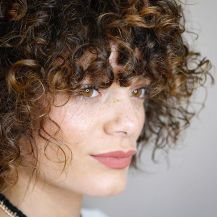 A Light Fringe Bang With Face-Framing Curls