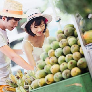 A male and female are shopping fruit at a local grocery store.