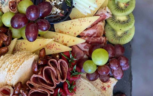 A charcuterie spread full of meats, cheeses, and fruits.