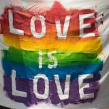 """A rainbow flag is painted on a white sheet that reads """"Love is love."""""""