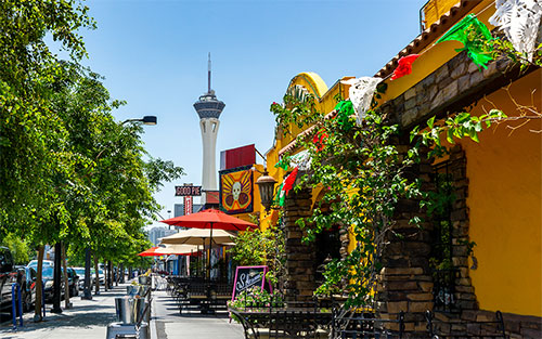 Downtown Las Vegas businesses are surrounded by vibrant umbrellas, greenery, and the Strip looms in the background.