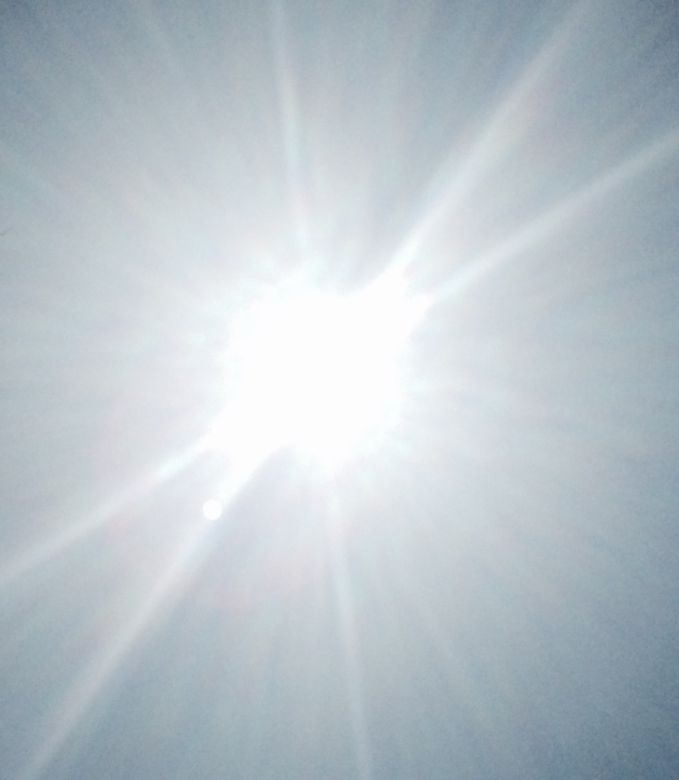 Brilliant white hot sun against blue sky