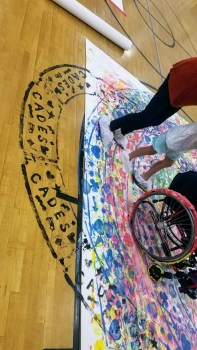 Wheelchair user creating a masterpiece using Zot Artz tools