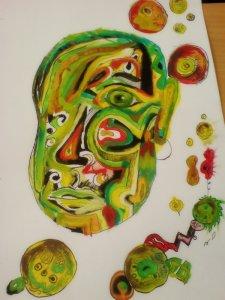Zelená hlava namalovaná akrylovkami na velkém výkresu, na hlavě je mnoho barevných žlutých a červených detailů, kolem hlavy je spousta barevných kruhů.