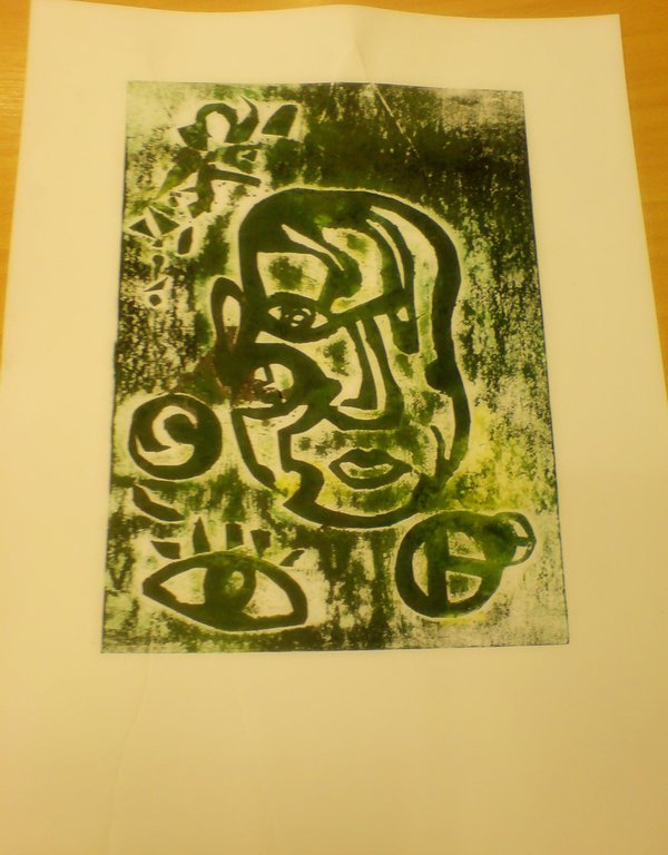 Tisk zelené figury hlavy v naivním stylu, kolem obličeje je i pár dalších očí a koleček.