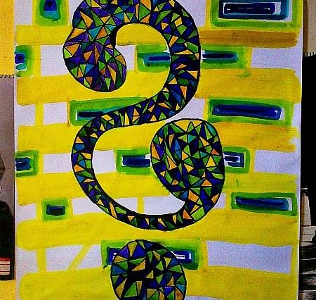 Velká malba otazníku složeného z modrých, žlutých a zelených plošek, trojúhelníkových. Pozadí je namalováno ze žlutých cihliček.