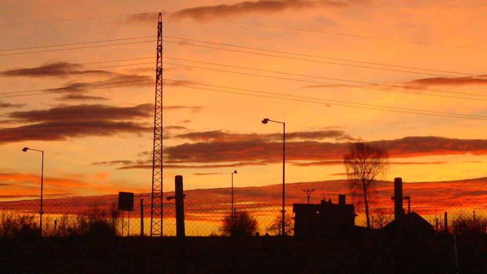 Fotografie zimního západu slunce - celá obloha je oranžová s červenými mraky, naproti nim vystupují černé siluety okolního domku a stromů a pouličních lamp.