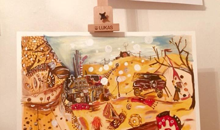 Na obrázku vidíme malířský stojan u bílé stěny. Na stojanu je papír, na kterém je namalována pouštní scéna s koberečky, podivným karavanem, opuštěnou továrnou a Zrzavou holkou, která pozoruje žonglující ženu u cirkusového stanu.