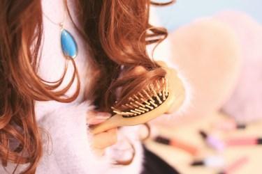 ブラシで髪の毛を丁寧にとかしている女の子の写真画像