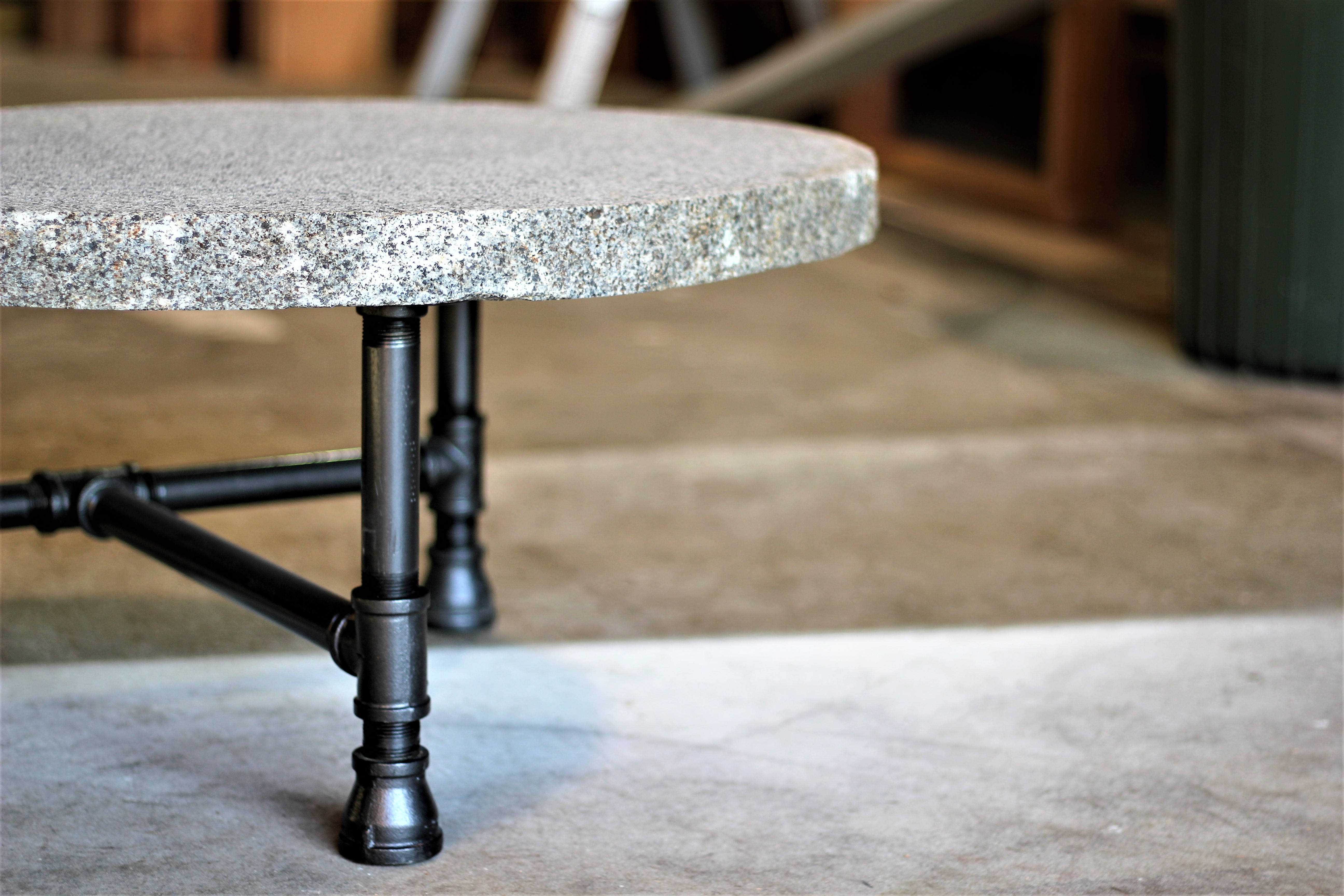 Granite slab coffee table with cast iron base