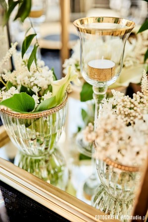 Wesele w motywie art deco the great gatsby organizowane przez Dariusz Zwadowski konsultant ślubny. Na zdjęciu czarny cekinowy obrus, złote podtalerze, krzesła chiavari, świece z złotą obwolutą, papeteria w kształcie sześcianu oraz duży bukiet z liści monstery i białych kwiatów