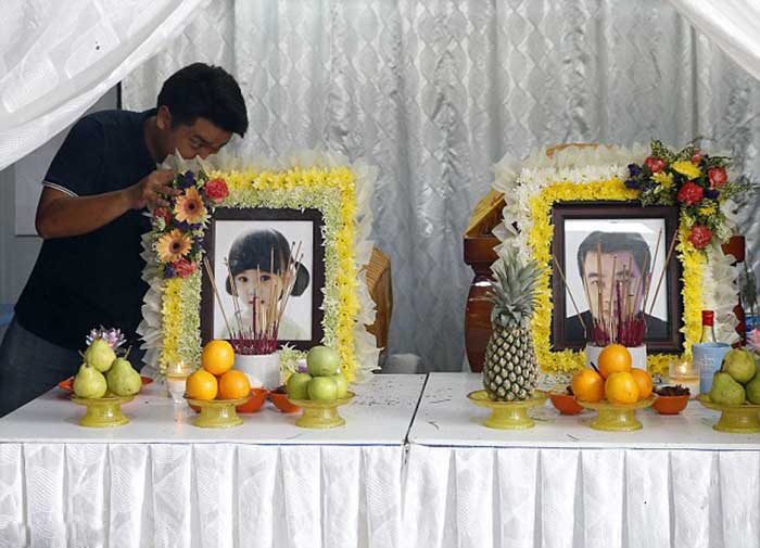 A family member places photographs of four-year-old Lee Jing Xuan and her father Lee Tze Siang in front of their coffins at their home in Butterworth, Malaysia, after they were killed in Monday's deadly blast