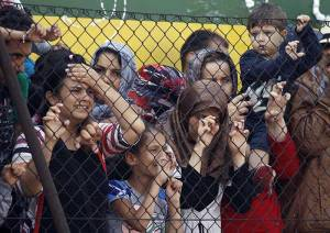 Migrants-stand-behind-a-fence-after-getting-off-a-train-that-was-stopped-in-Bicske,-Hungary,-as-police-try-to-shepherd-them-to-a-refugee-camp