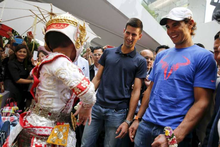 """Tennis players Novak Djokovic of Serbia and Rafael Nadal of Spain (R) look at a Thai folklore dancer as they visit a handicraft market before their """"Back To Thailand - Nadal vs Djokovic"""" friendly match on Friday, in Bangkok, Thailand, October 1, 2015. REUTERS/Jorge Silva"""