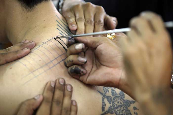 epa05219723 A Thai Buddhist monk using a steel rod with a sharp point to tattoo a man during the annual Magic Tattoo Festival at Wat Bangphra Buddhist temple in Nakhon Pathom province, Thailand, 19 March 2016. Thousands of tattooed men gathered for the annual festival at the Bangphra temple. The temple is famous for tattoos and amulets believed to provide strength and security as they were introduced by Buddhist monk, Luang Por Pern. EPA/NARONG SANGNAK