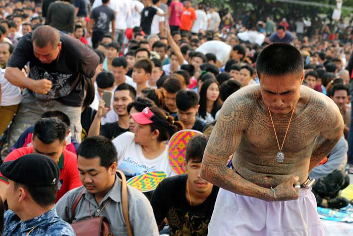 epa05219719 Thai devotees under the spell of a 'magic tattoo' participates in the annual Magic Tattoo Festival at Wat Bangphra Buddhist temple in Nakhon Pathom province, Thailand, 19 March 2016. Thousands of tattooed men gathered for the annual festival at the Bangphra temple. The temple is famous for tattoos and amulets believed to provide strength and security as they were introduced by Buddhist monk, Luang Por Pern. EPA/NARONG SANGNAK