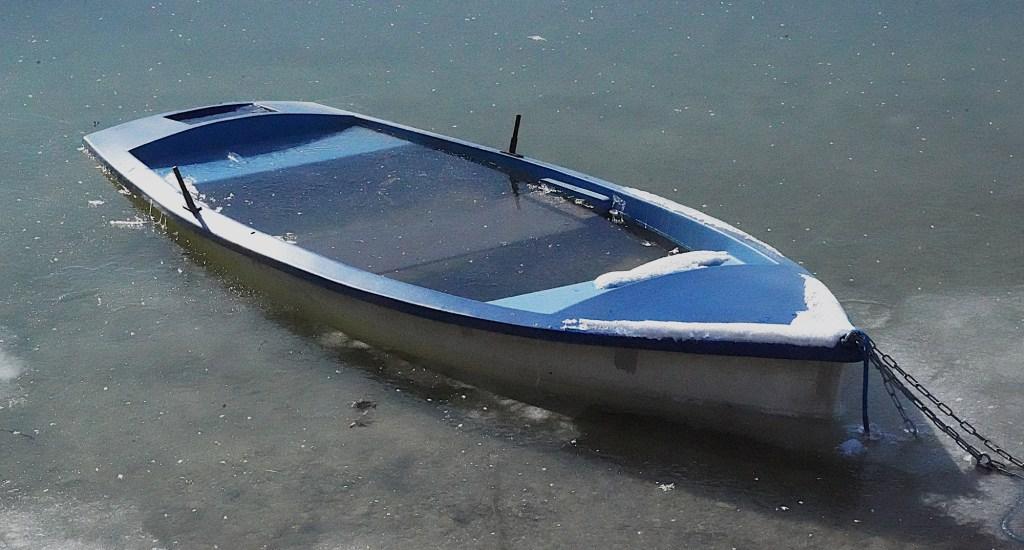 Kalt - Ruderboot voller Wasser im Eis
