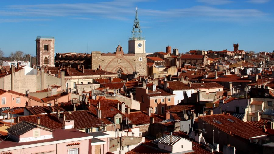 Blick vom Castillet über die Dächer von Perpignan. Im Hintergrund ist die Kathedrale mit ihrem berühmten Glockenturm zu sehen, der ebenfalls zu den Perpignan Sehenswürdigkeiten zählt.